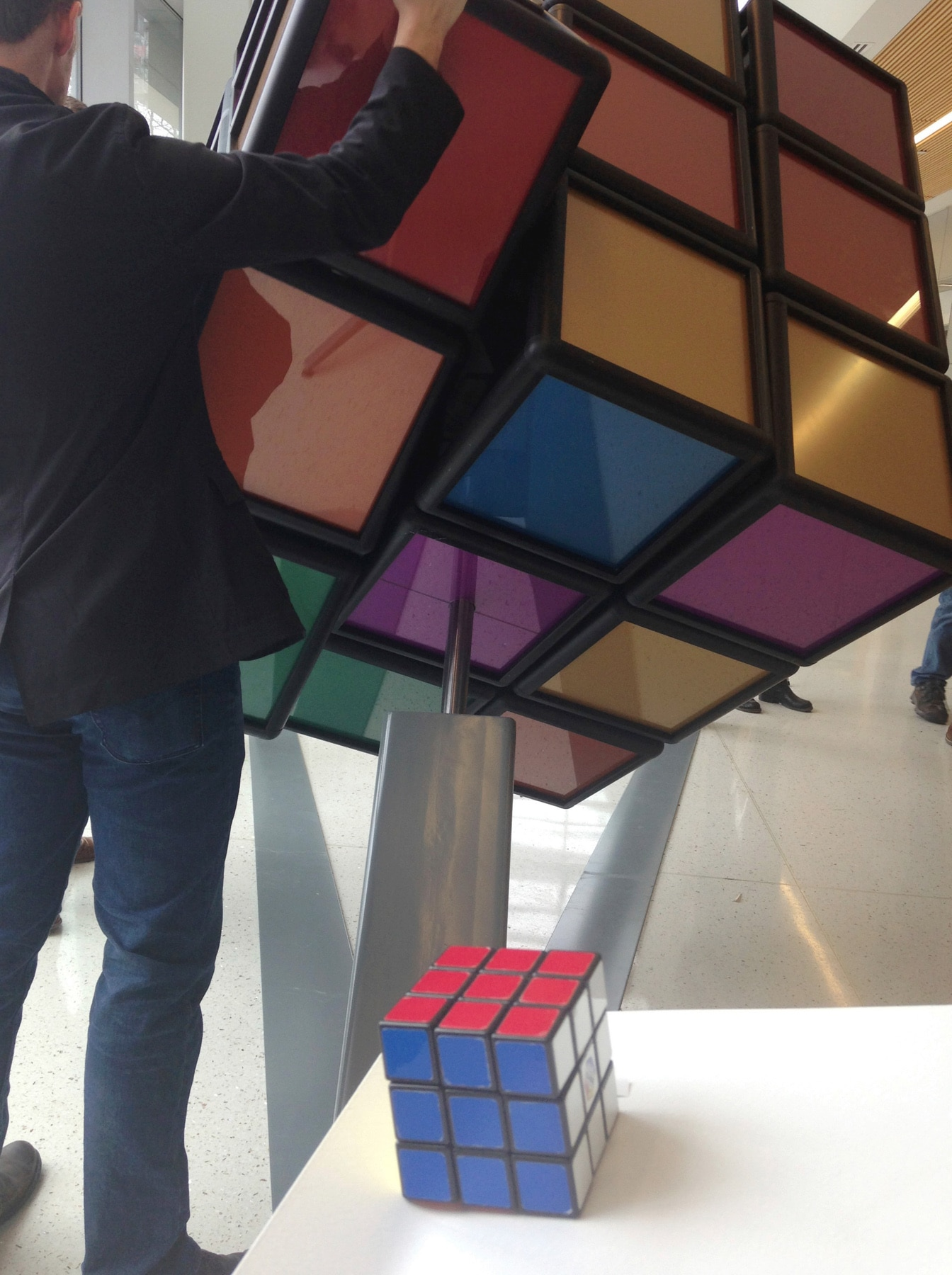 Person with a giant Rubik's Cube mounted on base (© AP Images)