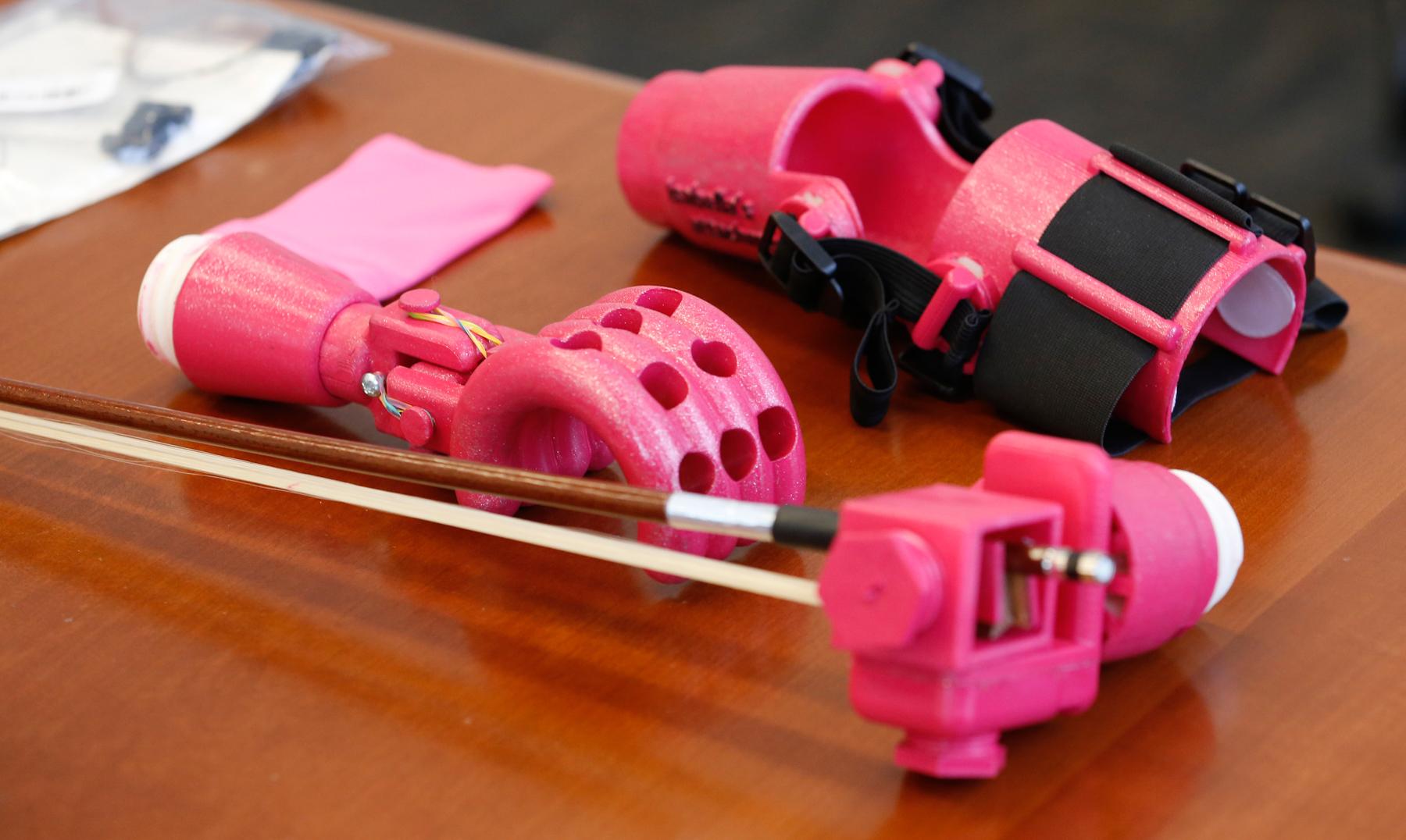 Mão protética de cor rosa segura arco de violino (© AP Images)