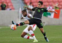 Dois jogadores de futebol tentam dominar a bola (© AP Images)