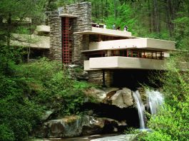 House in forest sitting atop waterfall (© AP Images)