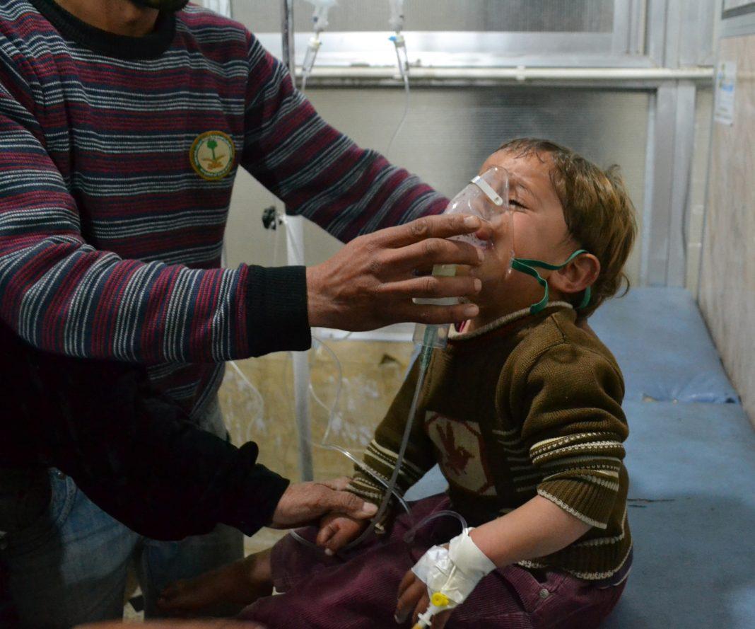 Criança síria recebendo oxigênio de um paramédico (© Getty Images)