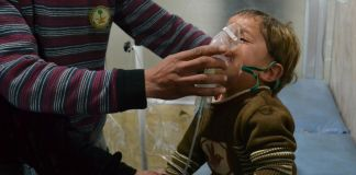 Syrian child receiving oxygen from a medic (© Getty Images)