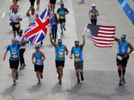 Ivan Castro and Karl Hinett finish the Boston Marathon (Photo by Jessica Rinaldi/The Boston Globe via Getty Images)