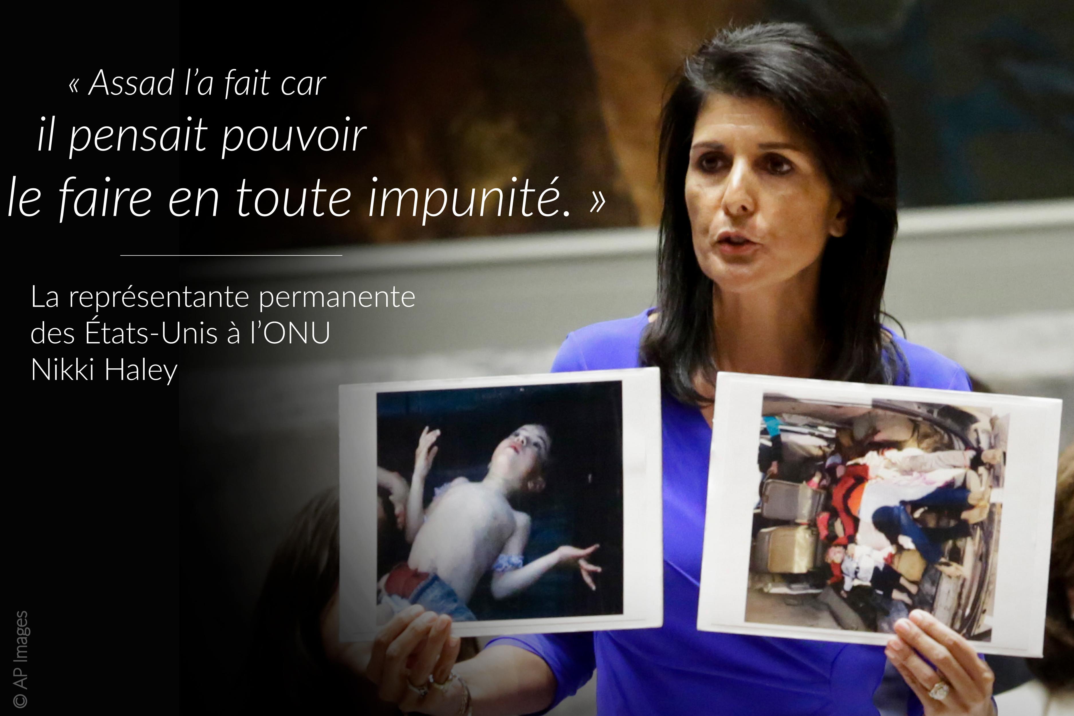 La représentante permanente des États-Unis à l'ONU Nikki Haley tenant des photos de victime de l'attaque à l'arme chimique ; sur sa gauche, une citation inscrite sur l'image (© AP Images)