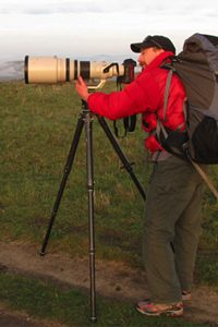 Man carrying large pack and looking through large camera on tripod (Courtesy of John Weller)