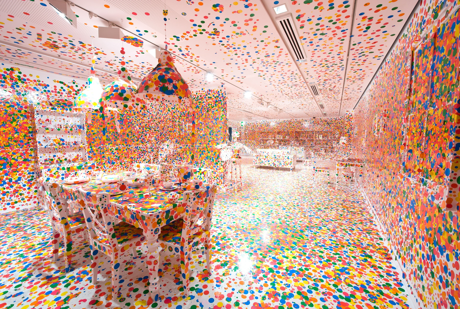 Room with dining table, chairs, bookshelves, lamps and other furniture covered with multicolored polka dots (Hirshhorn Museum)