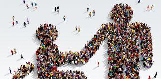 Personas agrupadas haciendo la forma de una persona en una silla de ruedas que le da la mano a otra (Shutterstock)