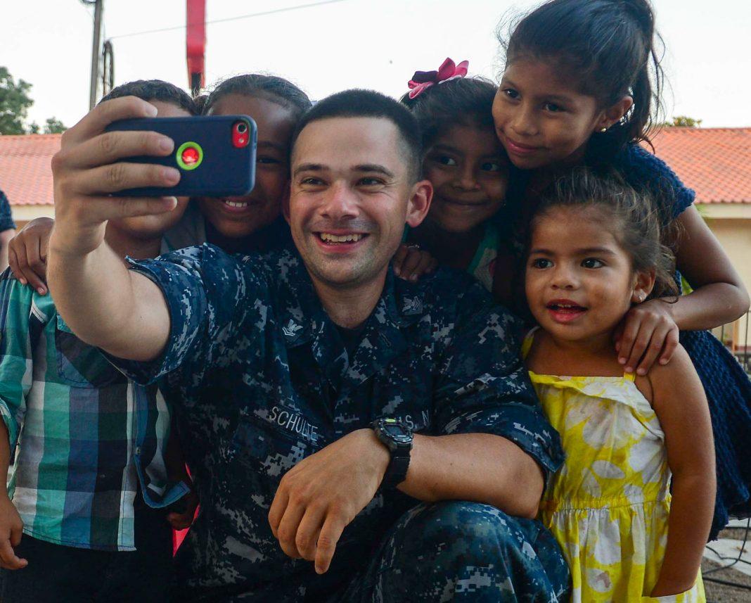 Marinero se toma una autofoto con algunos niños (U.S. Navy/Brittney Cannady)