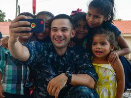 Marinheiro tira foto em modo selfie com crianças (Marinha dos EUA/Brittney Cannady)