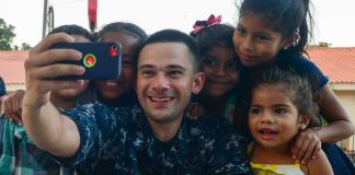 Sailor taking selfie picture with children (U.S. Navy/Brittney Cannady)