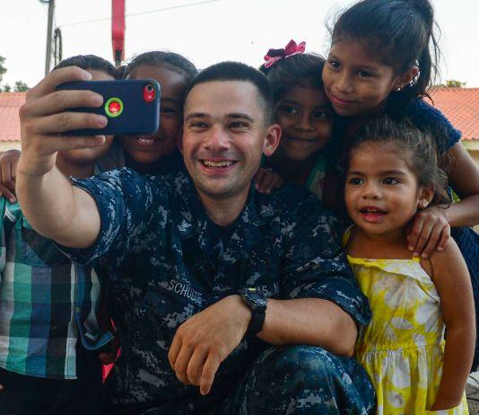 Sailor taking selfie picture with children (U.S. Navy/Brittney Cannady)