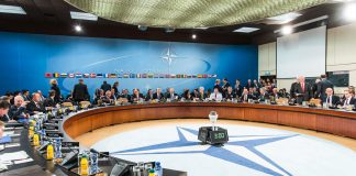 People sitting around large conference table (NATO)