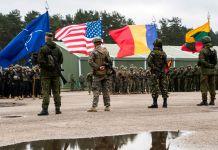 Quatro soldados segurando bandeiras refletidas em poça d'água (Corpo de Fuzileiros Navais dos EUA/sargento Kirstin Merrimarahajara)