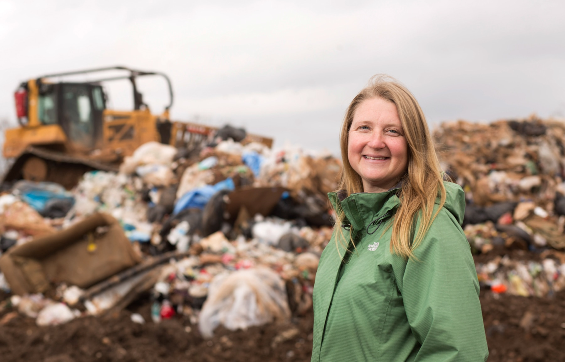 Jenna Jambeck smiling, with garbage mound and bulldozer in background (Courtesy of Jenna Jambeck)