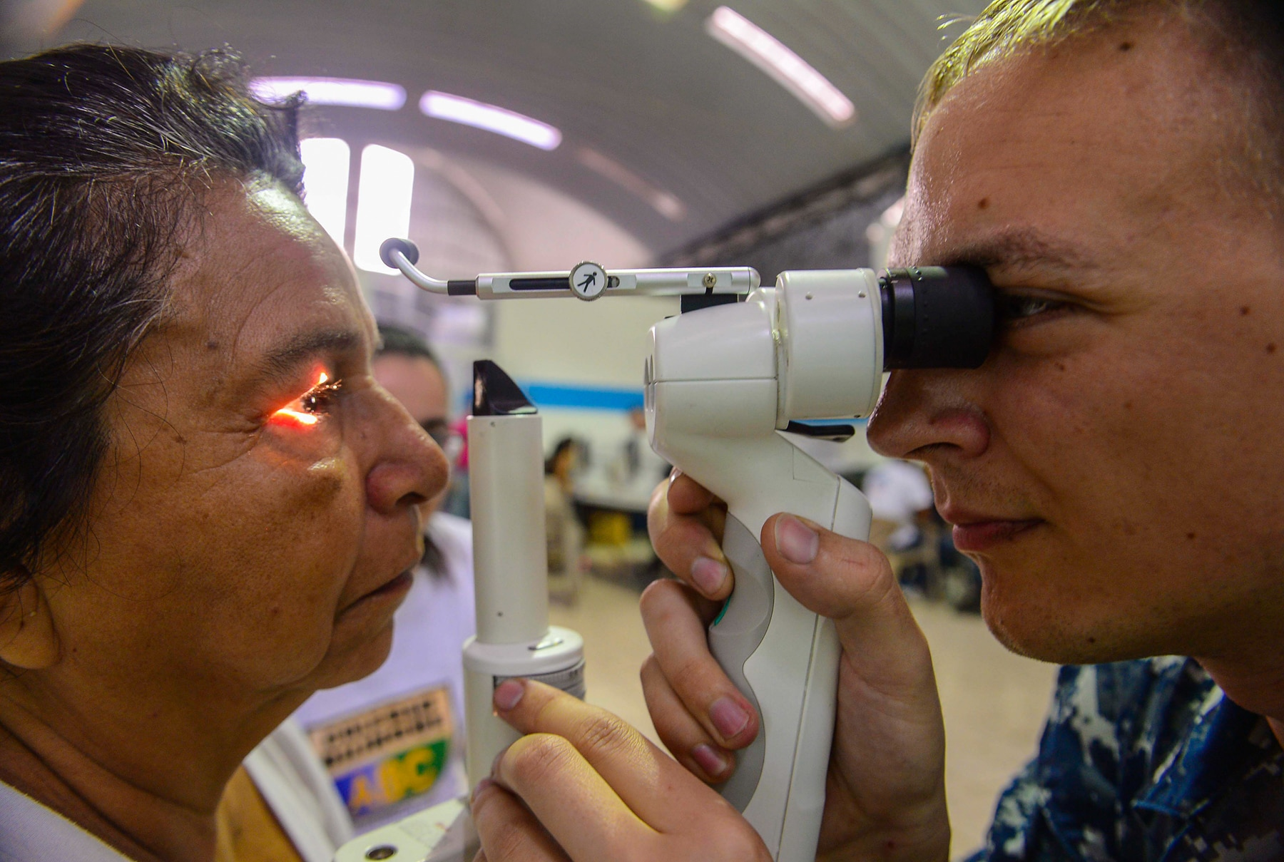Eye exam being performed by sailor on patient (U.S. Navy/ Brittney Cannady)