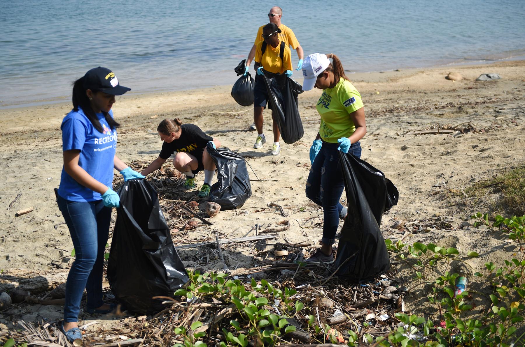 Personas recogen basura en la playa (U.S. Navy/Shamira Purifoy)