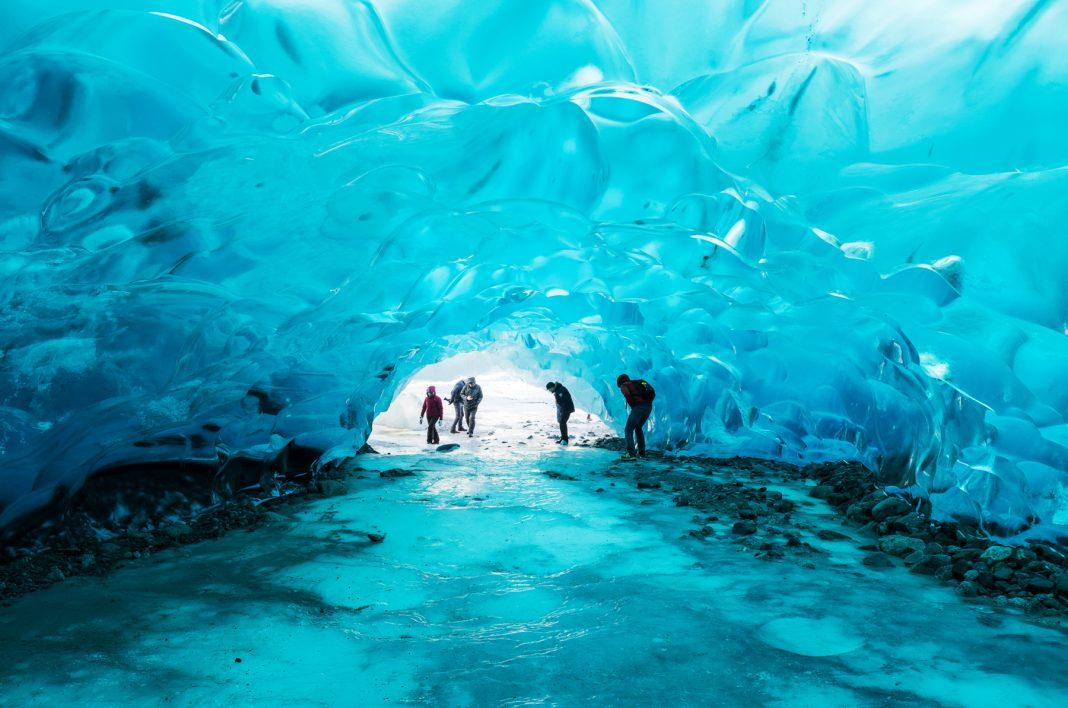 Pessoas se inclinam dentro de caverna em geleira (Secretariado do Conselho do Ártico/Linnea Nordström)