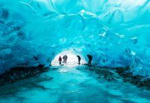 People crouching inside glacier cave (Arctic Council Secretariat/Linnea Nordström)