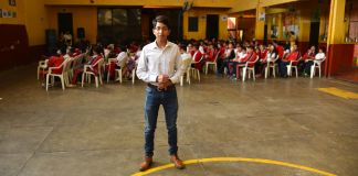 Young man posing for camera, standing to one side of group of seated students in gymnasium (U.S. Embassy of Guatemala)