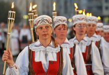 Women in traditional costumes holding torches (© AP Images)