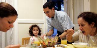Família sentada à mesa comendo (© AP Images)