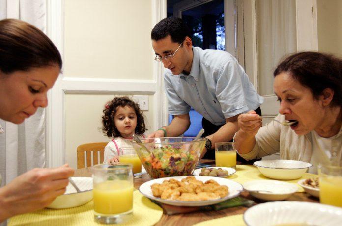 Familia sentada a la mesa comiendo (© AP Images)