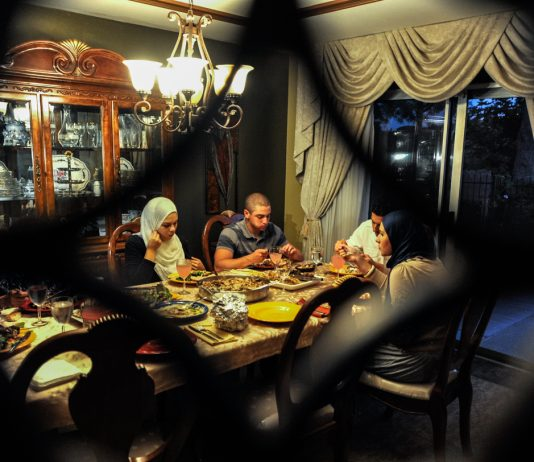 Family sitting at table eating (© AP Images)