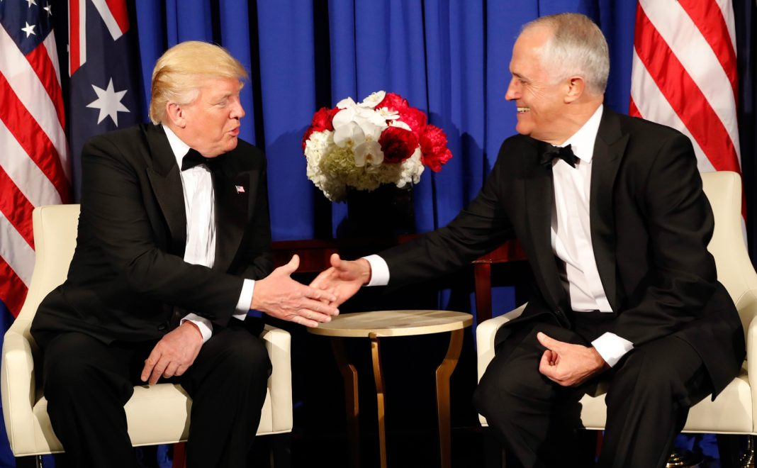 Presidente Trump e Malcom Turnbull sentados e apertando as mãos (© AP Images)