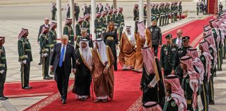 People walking down red carpeted tarmac (© AP Images)