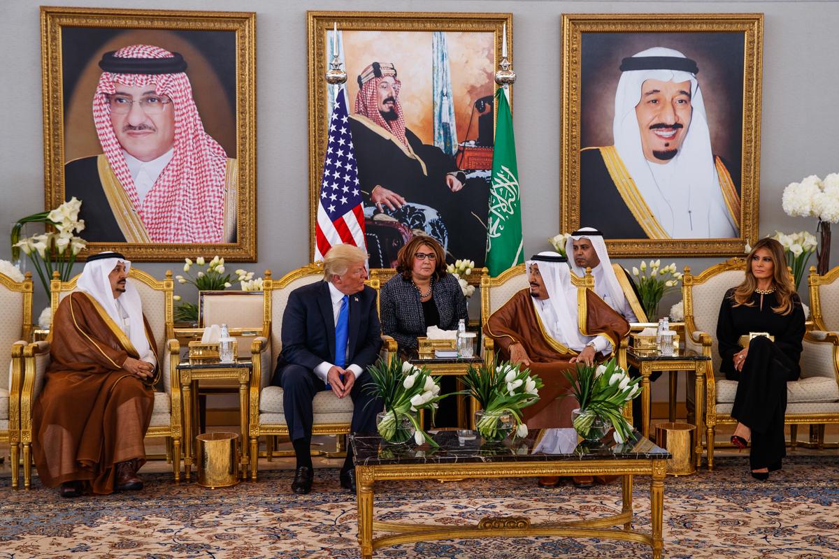唐纳德∙特朗普、梅拉尼娅∙特朗普和国王萨勒曼在座位上交谈。 (© AP Images)