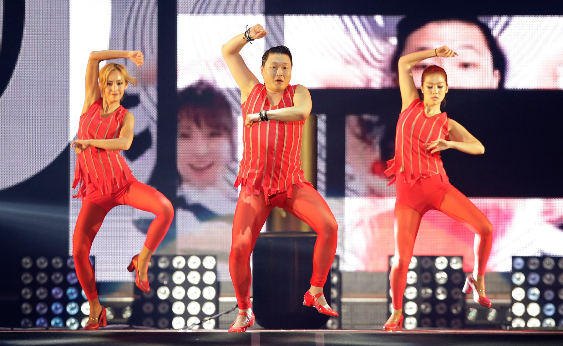 Psy and two women dancing (© AP Images)