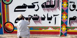 Man painting Urdu words on a wall (© AP Images)