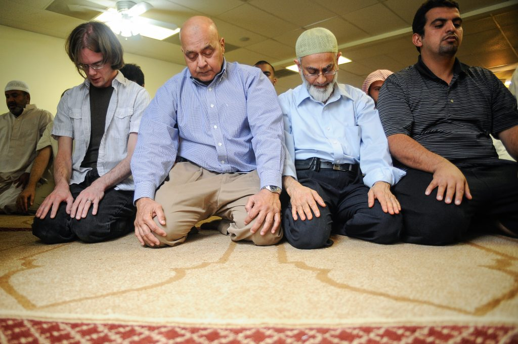 Men kneeling in prayer (© AP Images)