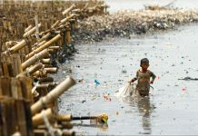 Child walking through trash-infested waters (© Solo Imaji/Barcroft Media via Getty Images)