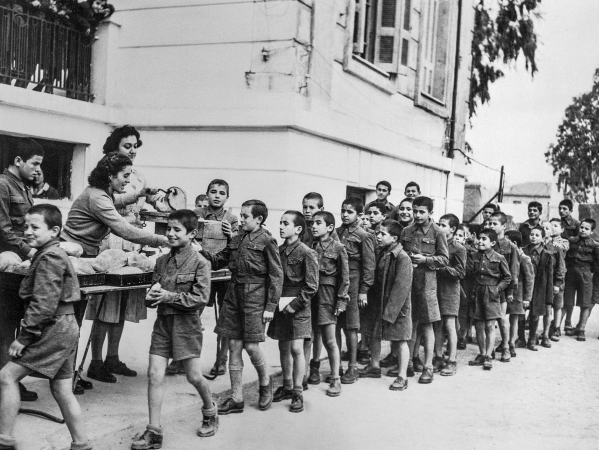Long line of children passing table and receiving food (© Bettmann/Getty Images)