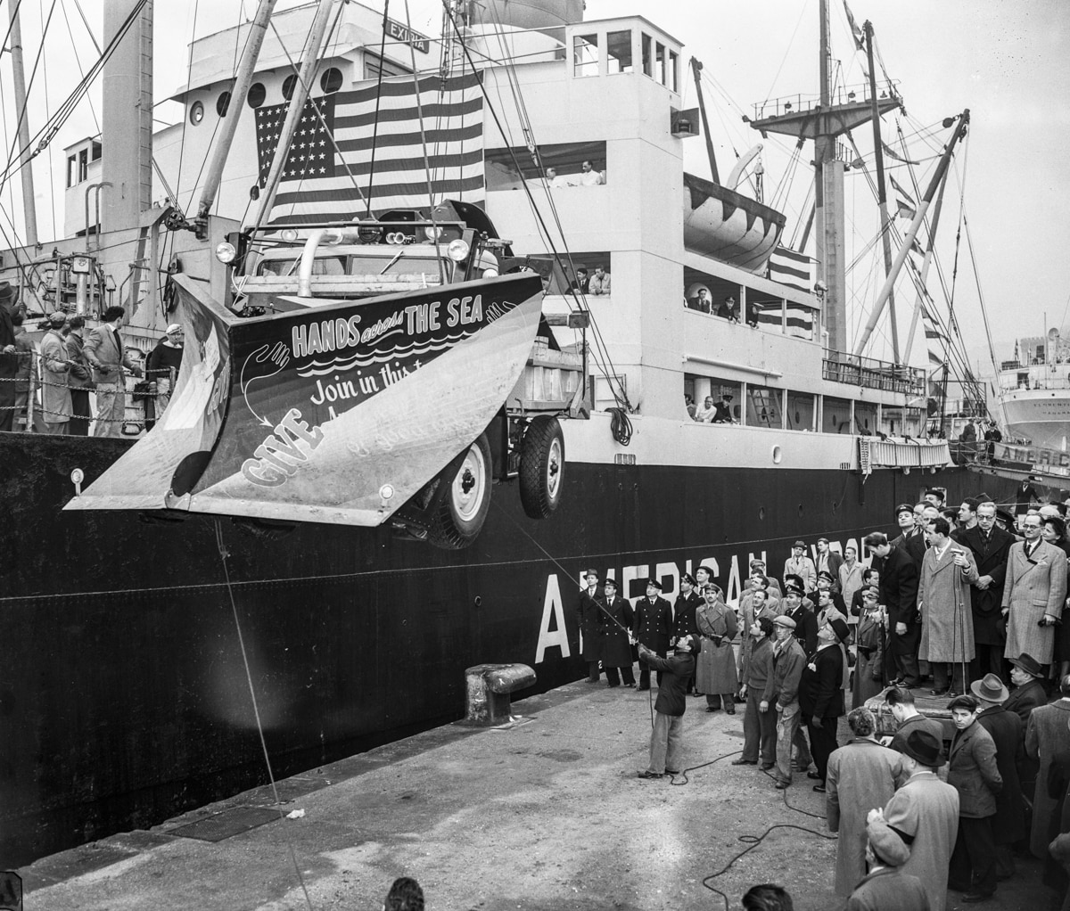 Vehicle being lowered from ship to dock crowded with people (© Bettmann/Getty Images)