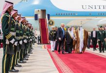 Many people standing on tarmac and walking away from airplane (© Bandar Algaloud/Saudi Royal Council/Anadolu/Getty Images)