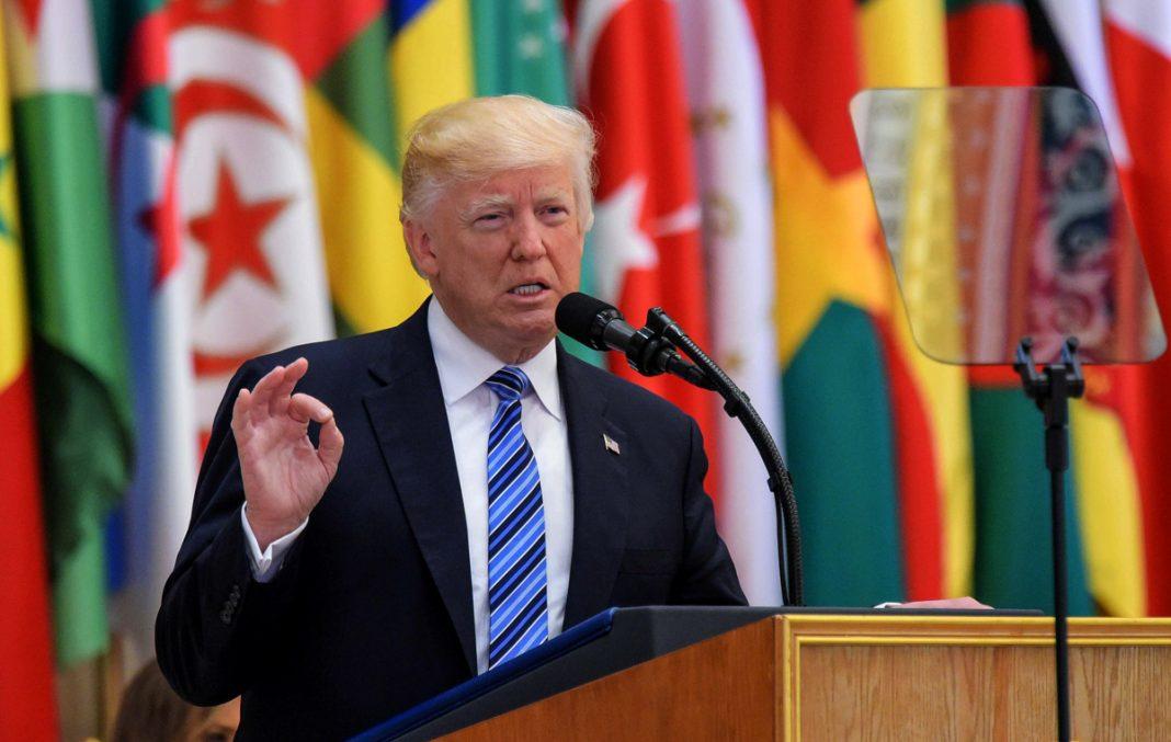 O presidente Trump discursa na tribuna com fileira de bandeiras ao fundo (© Mandel Ngan/AFP/Getty Images)