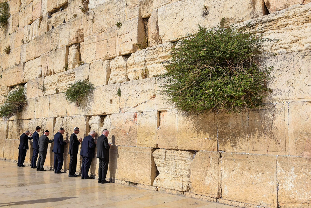 Seven people lined up along tall stone wall (© Mandel Ngan/AFP/Getty)