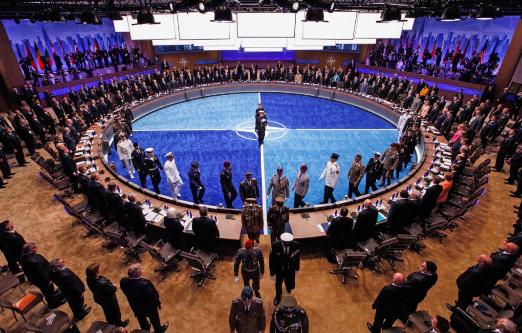 Grande salle de conférences avec des gens autour d'une table circulaire (© Reuters/Jim Young)