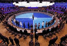 Large conference room filled with people surrounding circular table (© Reuters/Jim Young)