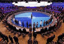 عده زیادی در یک تالار کنفرانس بزرگ بدور یک میزگرد ایستاده اند. (عکس از رویترز/جیم یانگ)