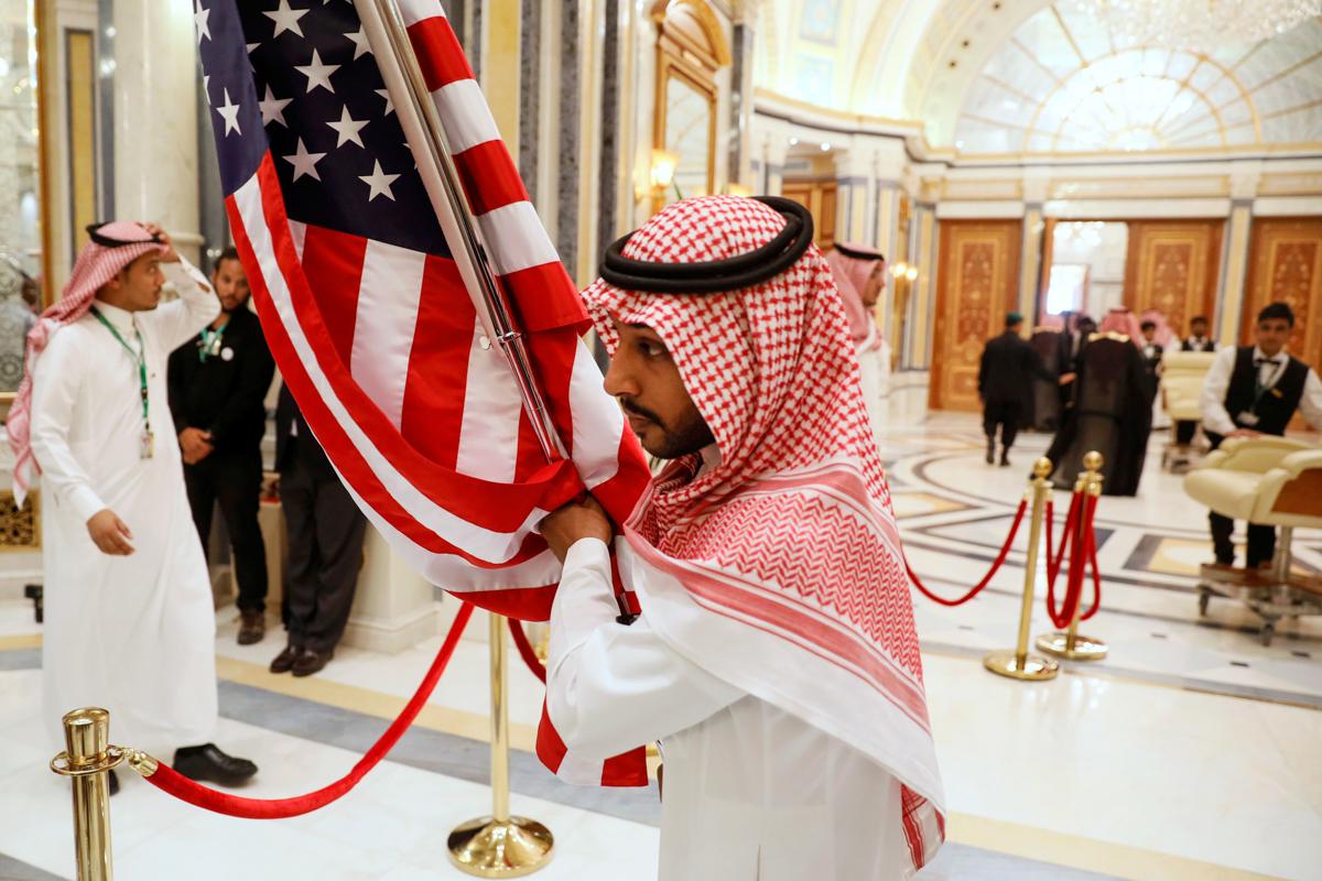手持美国国旗的工作人员。(© Jonathan Ernst/Reuters)