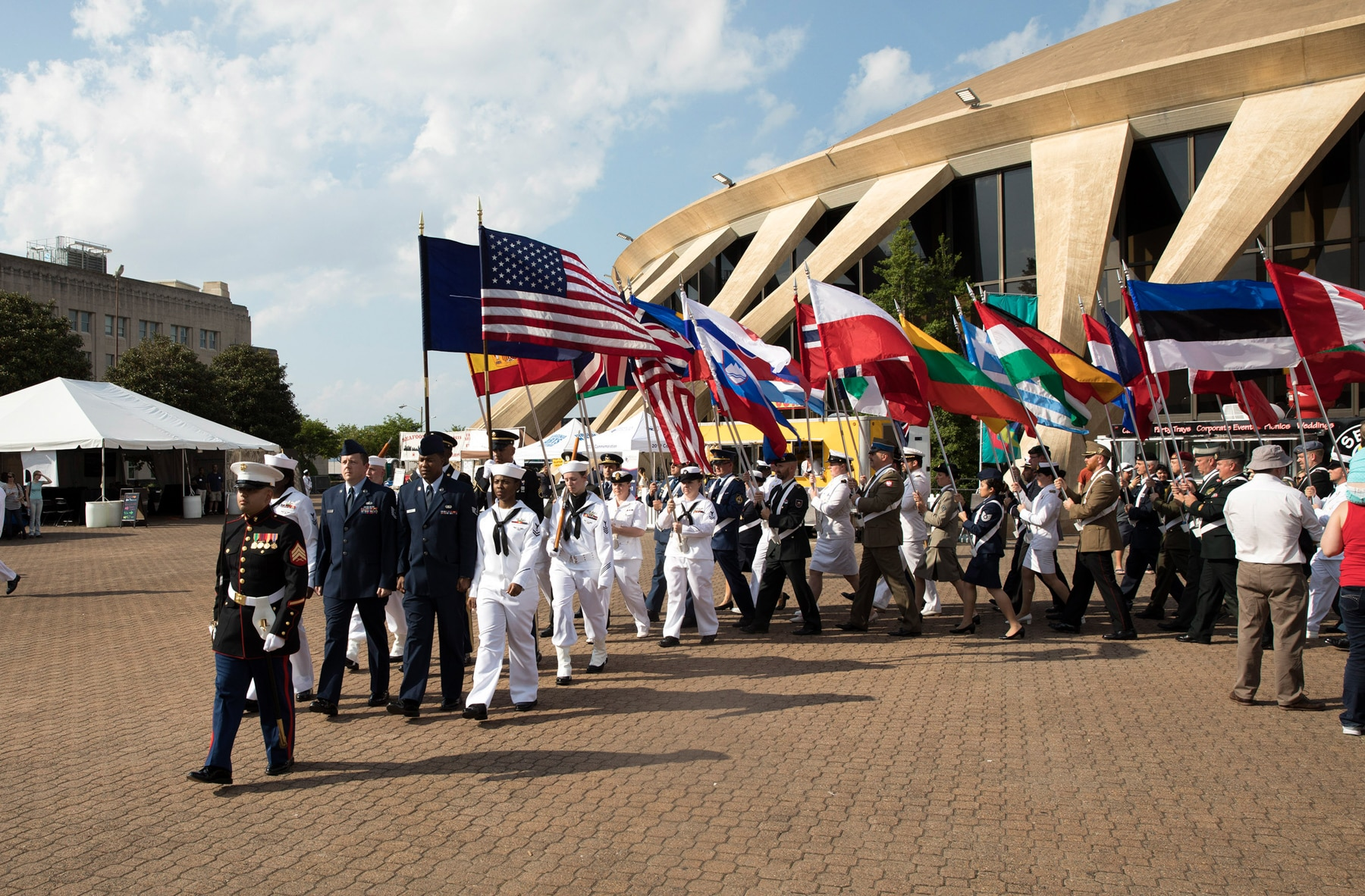 Military members marching in parade and carrying flags (U.S. Navy/Abraham Essenmacher)