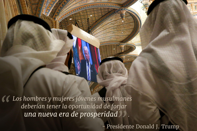 Personas observan al presidente Trump en televisión con texto superpuesto 'Los hombres y mujeres jóvenes musulmanes deberían tener la oportunidad de forjar una nueva era de prosperidad' (Jonathan Ernst/REUTERS)