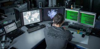 Homem sentado em frente de monitores de computador (Grupo Kudelski)