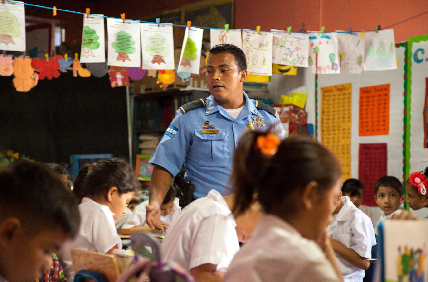 Police officer standing among children in classroom (U.S. Embassy Tegucigalpa/David Dulko)