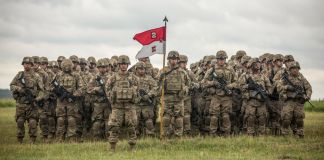 Group of soldiers standing in grass holding weapons and a flag (U.S. Army/Staff Sergeant Brian Kohl)