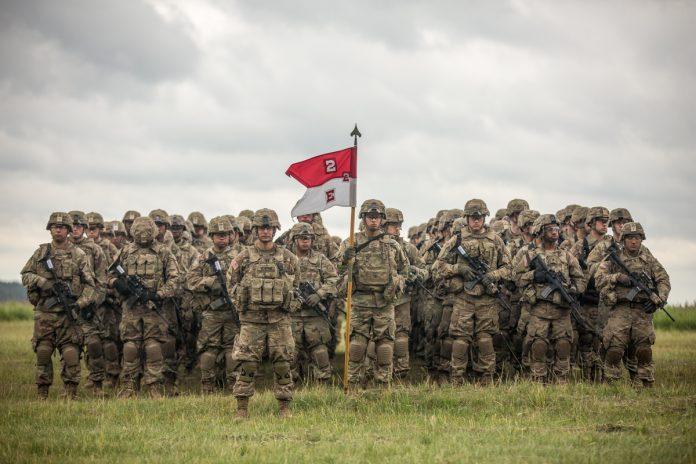 Groupes de soldats debout dans un champ, tenant des armes et un drapeau (U.S. Army/Staff Sergeant Brian Kohl)