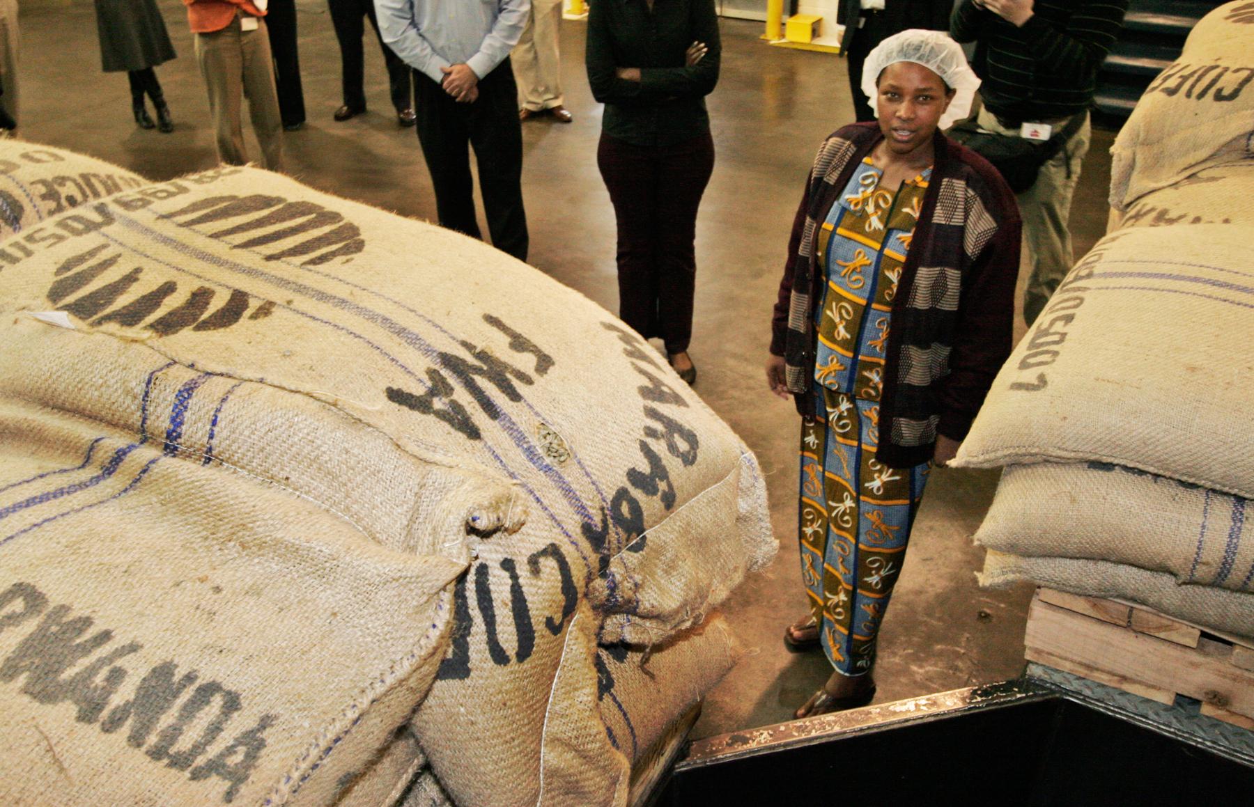 Woman standing between bags of coffee (© AP Images)